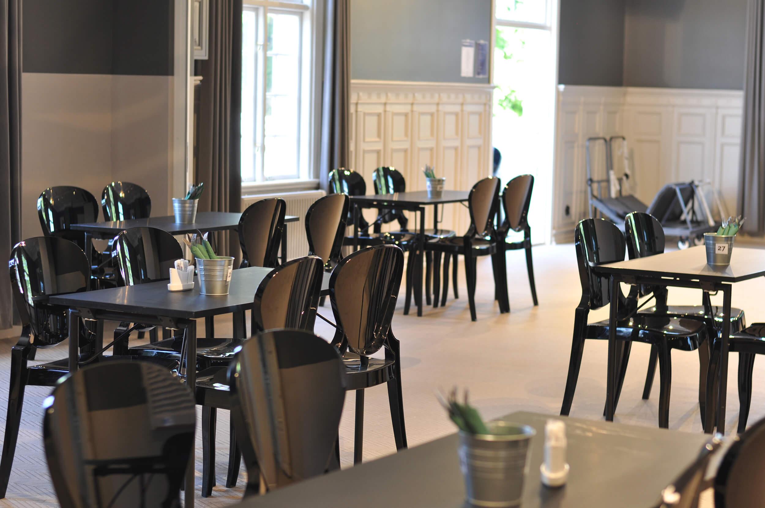 Bild på matsal med svarta bord och stolar
